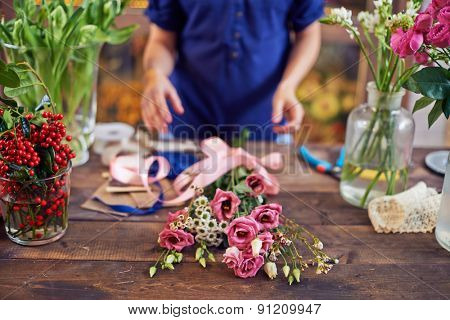 Bunch of flowers with pink ribbon with designer hands over it