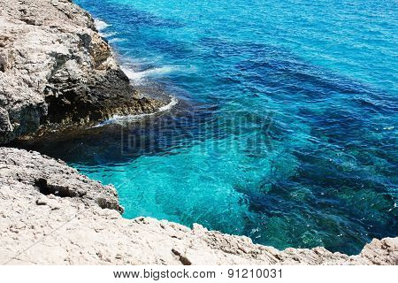 Transparent sea water. Rocky coast.