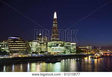 LONDON, UK - AUGUST 11, 2014: South walk of the river Thames in night lights. Modern Buildings view
