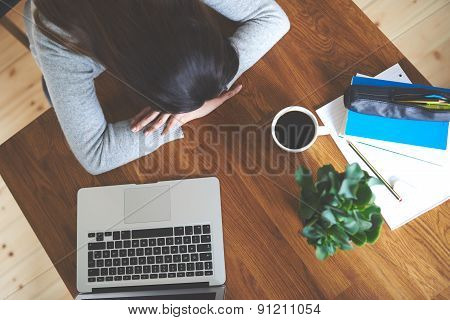 Woman Resting Head On Hands.