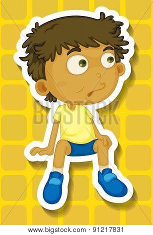 Closeup boy sitting on yellow background
