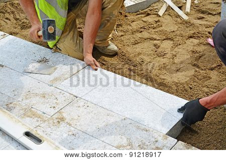Worker Tapping Paver Into Place With Rubber Mallet.