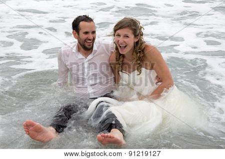 Lovely And Happy Newlywed Couple Standing In Water.