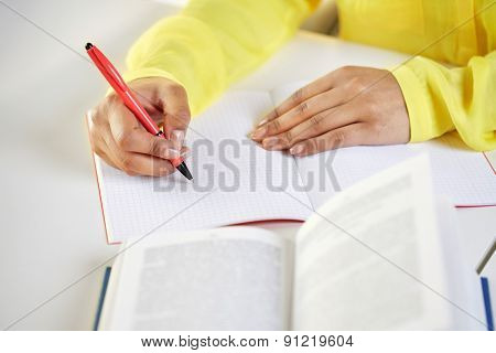people and education concept - close up of fafrican american female hands with book writing to notebook at school