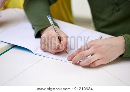 people and education concept - close up of male hands writing to notebook at school