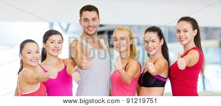 fitness, sport, training, gym and lifestyle concept - group of happy people in the gym showing thumbs up
