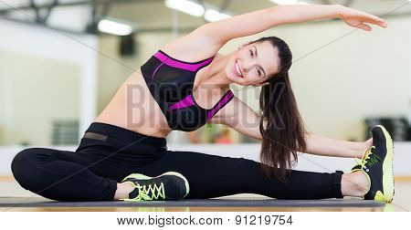 fitness, sport, training, gym and lifestyle concept - smiling teenage girl stretching on mat in the gym