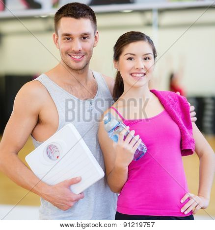 fitness, sport, training, gym and lifestyle concept - two smiling people with scale and water bottle in the gym