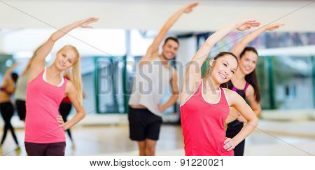 fitness, sport, training, gym and lifestyle concept - group of smiling people stretching in the gym