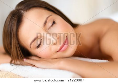 beauty and spa concept - beautiful woman with closed eyes in spa salon lying on the massage desk