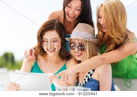 summer holidays, vacation, internet and technology - girls looking at tablet pc in cafe