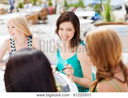 summer holidays and vacation - girls eating and drinking in cafe on the beach