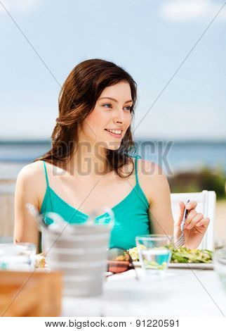 summer holidays and vacation - girl eating in cafe on the beach