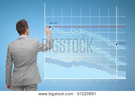 business, people, statistics and economical crisis concept - businessman drawing virtual chart from back over blue background