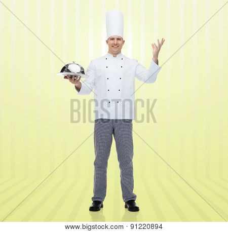 cooking, profession and people concept - happy male chef cook holding cloche over yellow background
