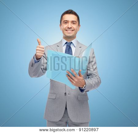 business, people, finances and paper work concept - happy smiling businessman in suit holding folder and showing thumbs up over blue background