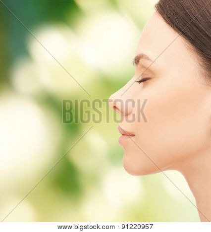 health, people and beauty concept - beautiful young woman face over green background