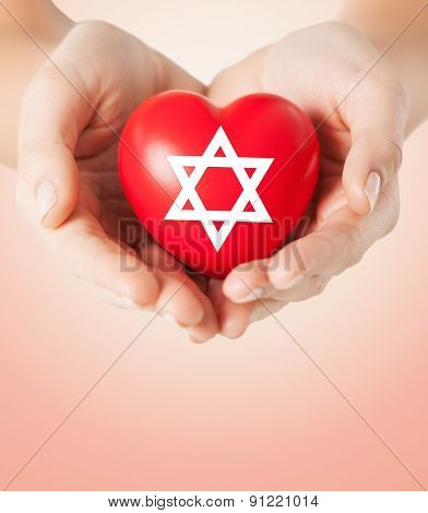 religion, christianity, jewish community and charity concept - close up of female hands holding red heart with star of david symbol over beige background