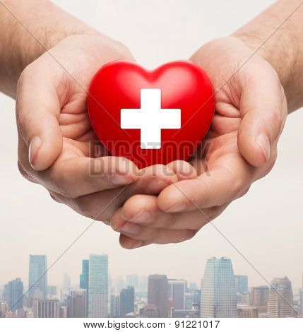 family health, charity and medicine concept - close up of male hands holding red heart with white cross over city skyscrapers background