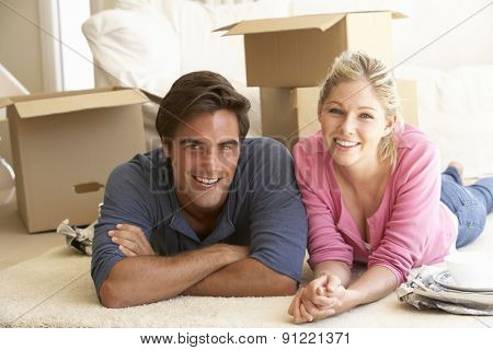 Young Couple Moving Into New Home Surrounded By Packing Boxes