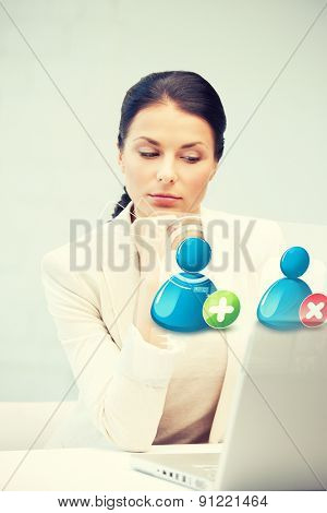 businesswoman looking at laptop with contact icon