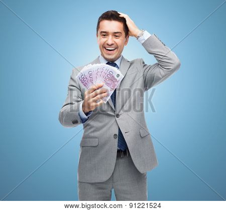 business, people and finances concept - happy laughing businessman with euro money over blue background