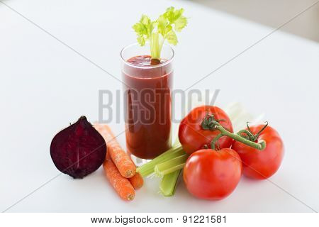 healthy eating, organic food and diet concept - close up of fresh juice glass and vegetables on table