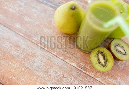 healthy eating, organic food and diet concept - close up of fresh green juice glass and fruits on table