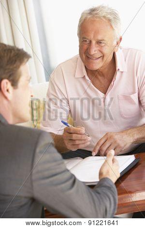 Senior Man Meeting With Financial Advisor At Home