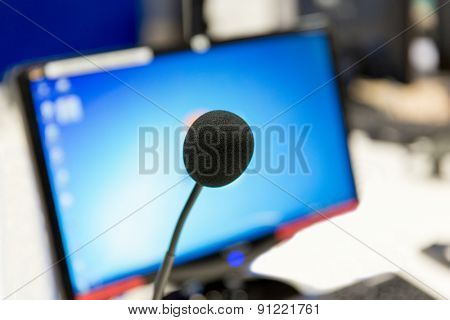 technology, electronics and audio equipment concept - close up of microphone and computer monitor at recording studio or radio station