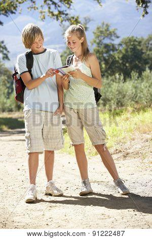 Teenage Couple Hiking Through Countryside