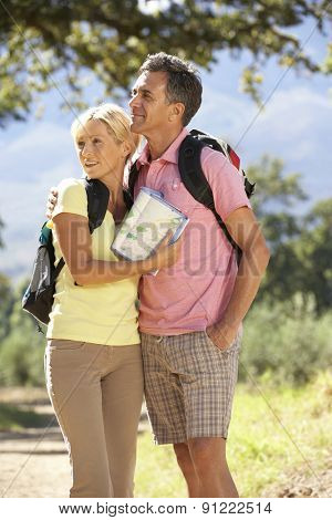 Middle Aged Couple Hiking Through Countryside