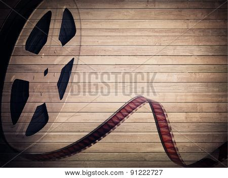 Grunge old motion picture reel with film strip on brown wooden planks. Vintage background