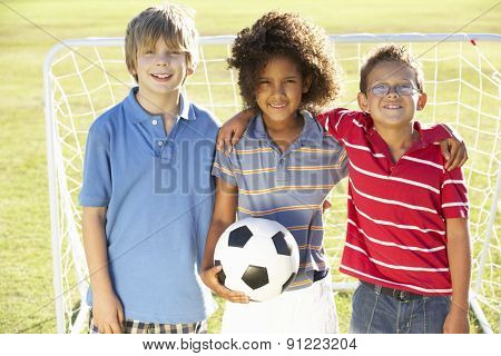 Young Boy With Soccer Ball Standing By Goal