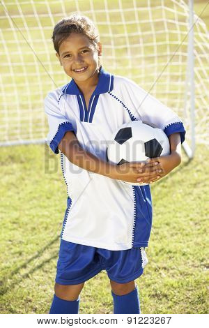 Young Girl Dressed In Soccer Kit Standing By Goal