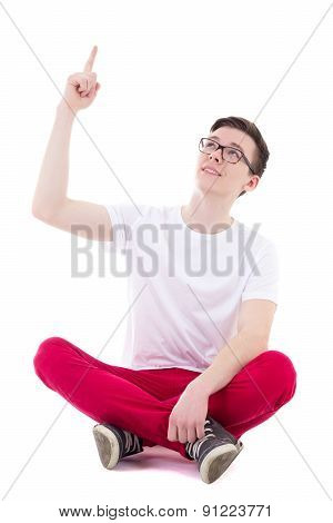Young Handsome Man In White T-shirt Sitting And Pointing At Something Isolated On White