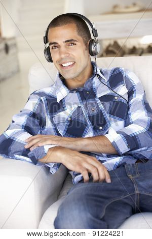 Young Man Relaxing Listening To Music At Home