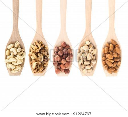 Wooden spoons full of different nuts