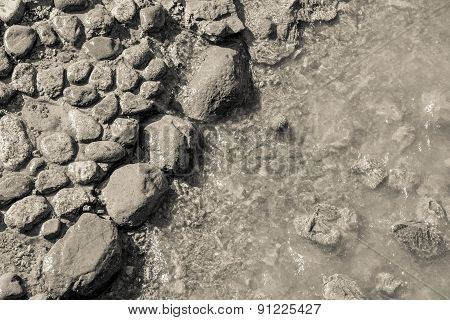 Beige Background And Dirty Stones On The Coast