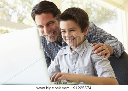 Hispanic Father And Son Using Laptop