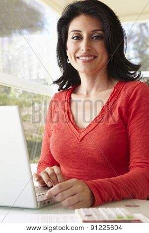 Hispanic Woman Using Laptop In Home Office