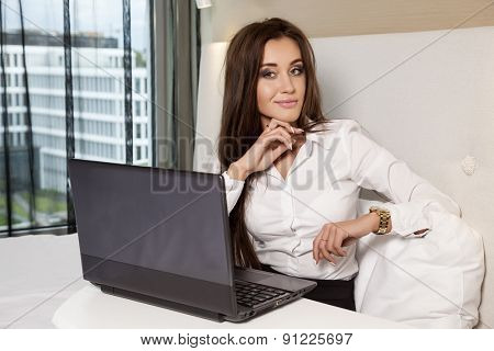 Young adult beauty attractive sexy and sensuality happy pretty brunette businesswoman using laptop while lying on bed in hotel room