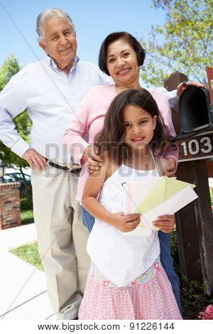 Hispanic Grandparents And Granddaughter Checking Mailbox