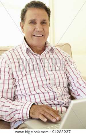 Senior Hispanic Man Using Laptop At Home