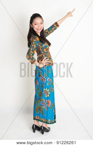 Full body portrait of happy Southeast Asian woman in batik dress finger pointing away, standing on plain background.