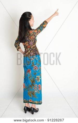 Full body rear view of Southeast Asian woman in batik dress finger pointing away, standing on plain background.