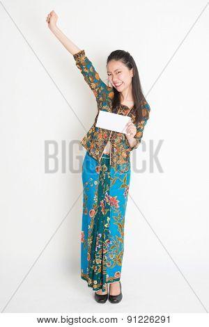 Full length portrait of Southeast Asian female in batik dress hands holding an envelope smiling, standing on plain background.