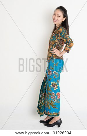 Full length cheerful Southeast Asian female in batik dress standing on plain background.