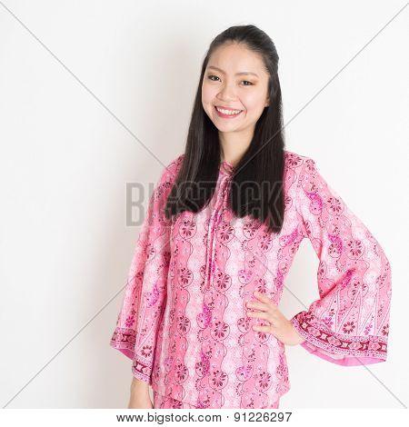 Portrait of happy Southeast Asian woman in pink batik dress standing on plain background.