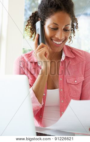 Young Woman On Phone Using Laptop At Home